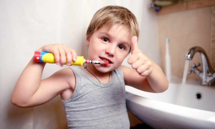 the child brushes his teeth with an electric toothbrush